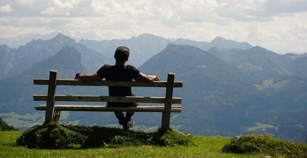 Marco Sison of Nomadic FIRE sitting on a bench on top of the Austrian Alps