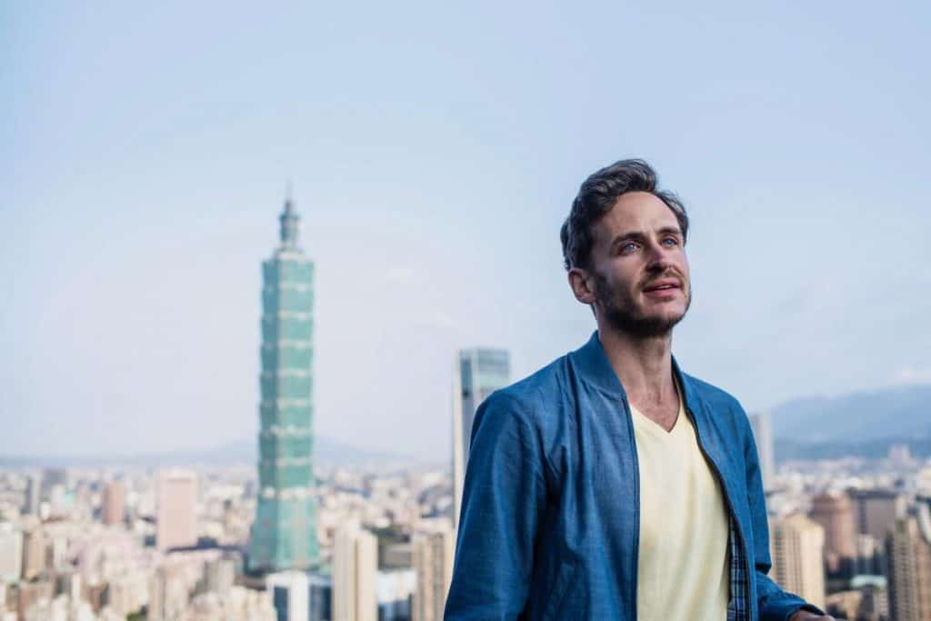 man in front of the Taipei 101 building the tallest building in Taiwan